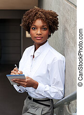 pretty African American executive sitting outside with pen...