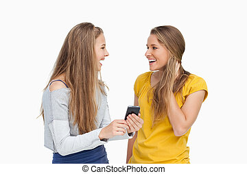 Two surprised young women holding a smartphone