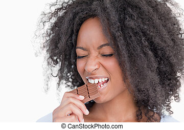 Young woman closing her eyes while eating chocolate against...