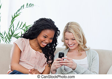 A woman is showing her friend her mobile phone