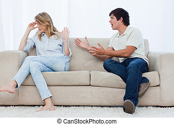 A man sitting on a couch is having an argument with his...