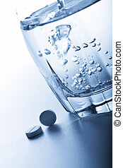 aspirin pills and glass of water toned blue