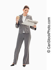 Businesswoman reading newspaper and holding coffee - A...