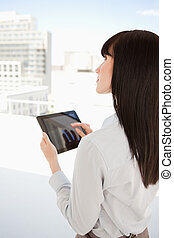 Woman looking up as she uses her tablet pc - A business...