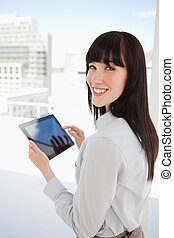 A smiling woman looking into the camera as she has a tablet pc in her hands