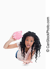 A worried young woman holding an empty piggy bank - A...
