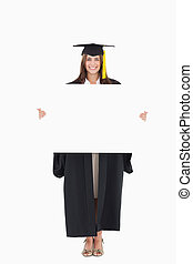 A full length shot of a woman holding a blank sheet in her hands as she smiles and looks at the camera