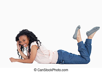 A smiling young woman is lying on the floor talking on her mobile phone against a white background