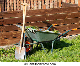 Gardening - Full barrow with gloves a spade and a garden...