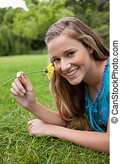Young smiling woman smelling a yellow flower while lying down in the countryside