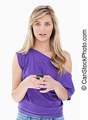 Surprised blonde woman holding her cellphone