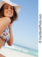 Smiling young woman proudly standing in front of the ocean