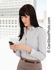 A woman at work uses her phone to text - A woman using her...