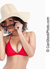 Young woman in beachwear putting on her sunglasses