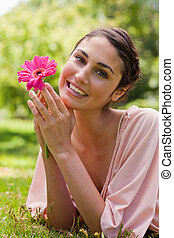 Woman restling her chin on her hands while holding a flower...