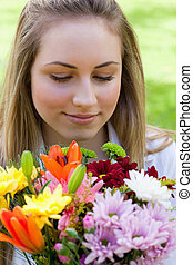 Young relaxed blonde girl smelling a beautiful bunch of flowers while closing her eyes