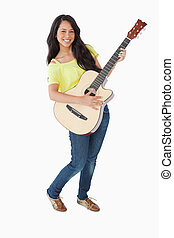 Young Latino woman holding a guitar