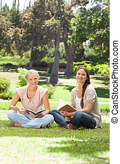 Smiling women with their books sitting in the park