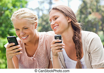 Smiling friend with cellphones - Smiling female friends with...
