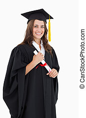 A smiling woman with her degree as she looks at the camera