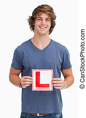 Smiling young man holding a learner driver sign