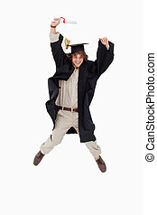 Male student in graduate robe jumping against white...