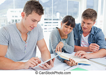 A smiling group of students using a book and a tablet to get...