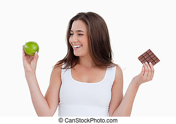 Smiling young woman looking at a green apple