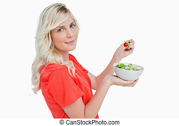 Side view of a young blonde woman eating vegetable salad
