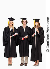 Three students in graduate robe holding a diploma