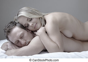 Nude Couple - Young and fit caucasian adult couple lying on...