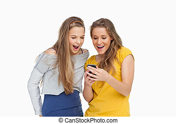 Two voiceless young women looking a smartphone against white...