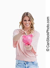 Woman holding a piggy bank is putting money into it - A...