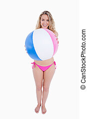 Smiling young woman holding a beach ball in front of her