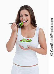Smiling young woman eating a salad