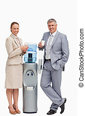 Portrait of business people smiling next to the water dispenser against white background