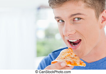 A man with a slice of pizza in his hand as he looks at the camera