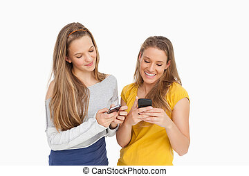 Two young women texting on their cellphones against white...