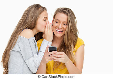 Young woman whispering to her friend whos texting on her...