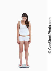 Young woman looking at her weighing scales against a white...