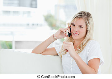 A woman looking at the camera as she talks on the phone - A...