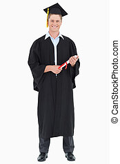 A male graduate with his degree in hand - A smiling graduate...