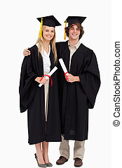 Two students in graduate robe shoulder to shoulder