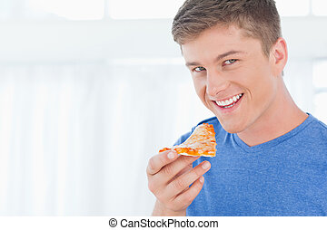 A man with a piece of pizza as he looks at the camera