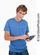 Portrait of a young man using a calculator against white...