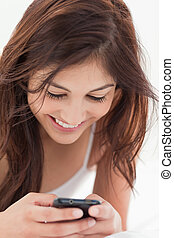 Close up, woman using her smartphone and smiling - A close...