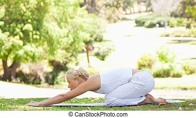 Side view of a woman doing stretches in the park