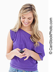 Smiling blonde woman holding her cellphone
