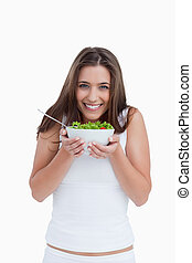 Happy brunette woman looking at the camera while holding a bowl of salad