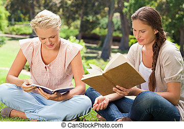 Friends reading books in the park